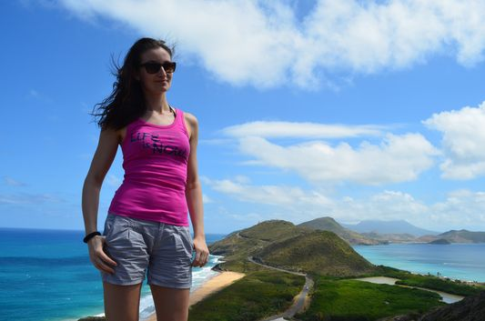 with South East Peninsula of St. Kitts behind crazy sexy fun traveler