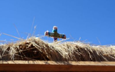 a-colourful-cross-on-top-of-the-straw-roof-of-machuca-houses