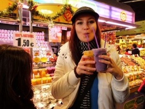 crazy sexy fun traveler drinking fruit juices in la Boqueria market in Barcelona