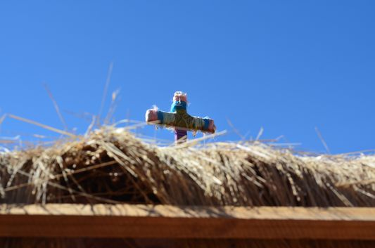 a colourful cross on top of the straw roof of Machuca houses