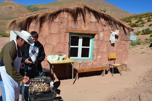 an Atacameño man preparing anticuchos de llama