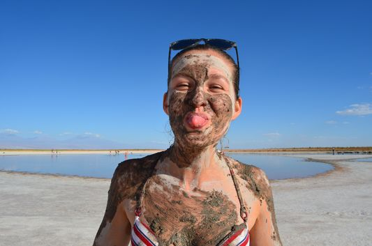 crazy sexy fun traveler showing the tongue off covered all with mud