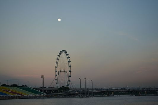 Singapore flyer with full moon above