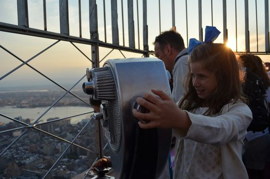 a cute little girl on top of the Empire State Building