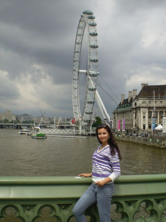 crazy sexy fun traveler with the London Eye behind just before another storm
