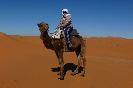 Kami riding a camel in Sahara