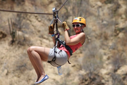 Wild Canyon zip line in seated position with knees up