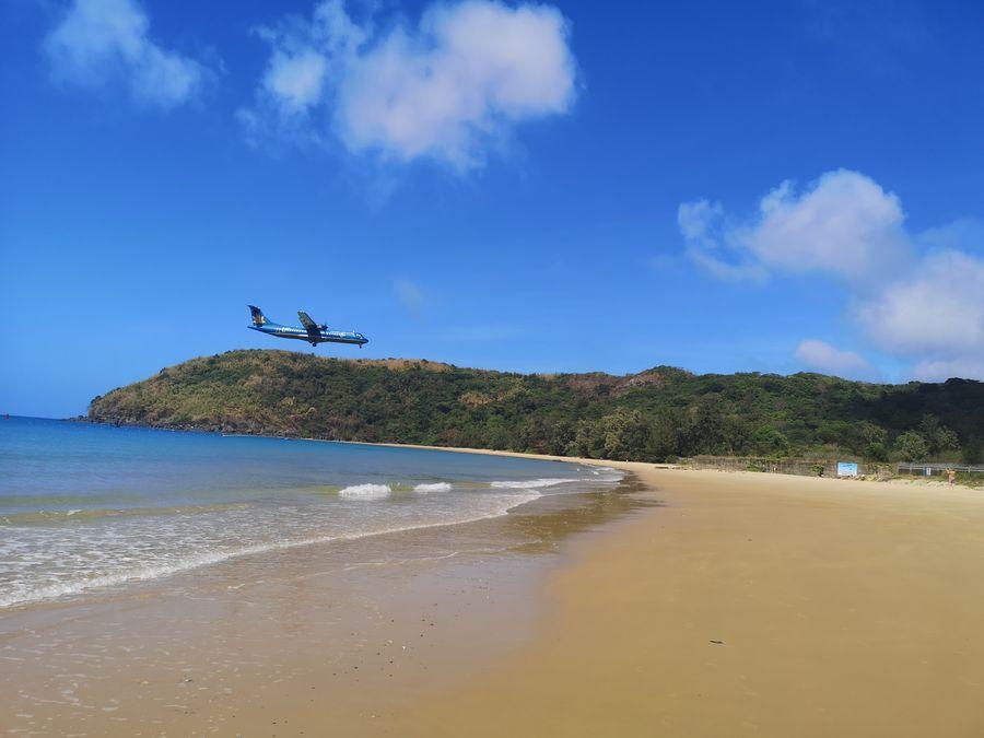 an airplane flying over Dam Trau beach Con Dao